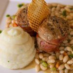 Twin Pork Mignon wrapped in prosciutto and served with whipped parsnip potatoes and stewed white beans